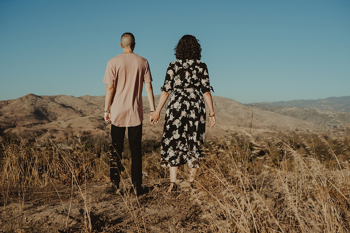 Orange County family photographer. portrait of couple standing away from the camera and looking out at the hills while holding hands at Irvine Regional Park Orange County