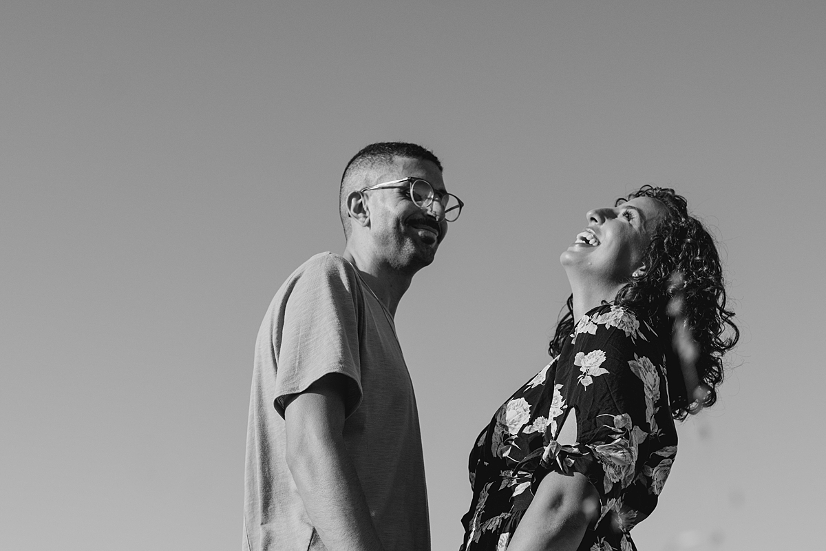 Orange County family photographer. black and white portrait of couple laughing during outdoor couples photo shoot at Irvine Regional Park Orange County