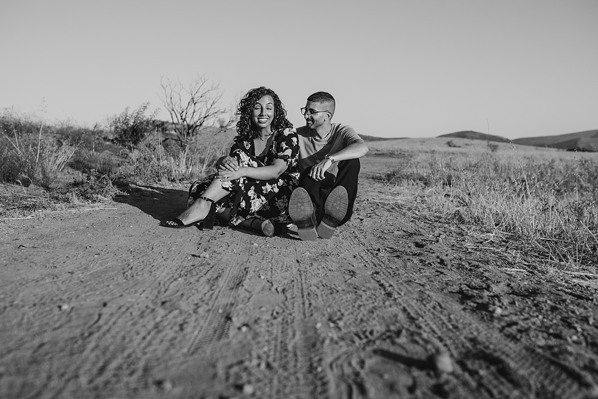 Orange County family photographer. candid black and white portrait of couple sitting on a dirt road while laughing at Irvine Regional Park Orange County