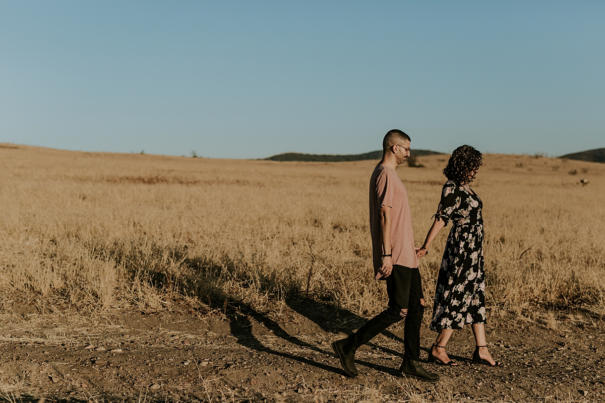 Orange County family photographer. photo of couple walking hand in hand along a dirt road at sunset during couple's photo session at Irvine Regional Park Orange County