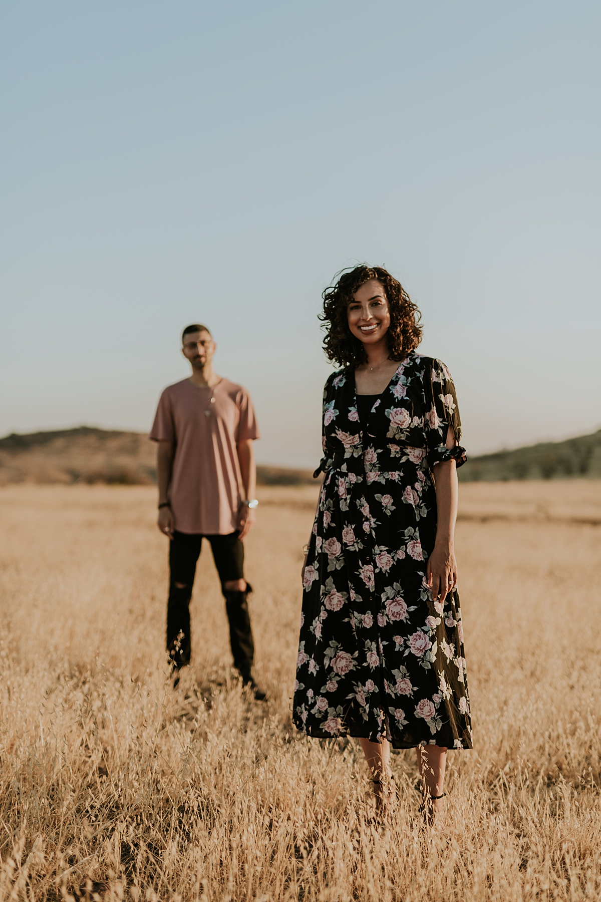 Orange County family photographer. portrait of married standing in the yellow fields at sunset during couple's photo session at Irvine Regional Park