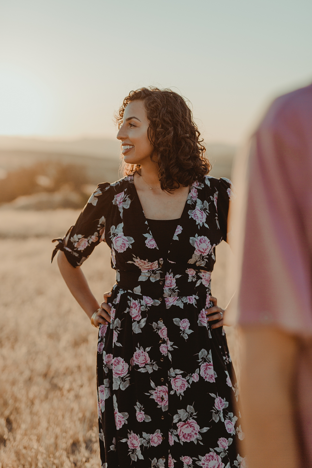 Orange County family photographer. candid photo of wife standing in fields with hands on hips and husband in edge of frame at Irvine Regional Park