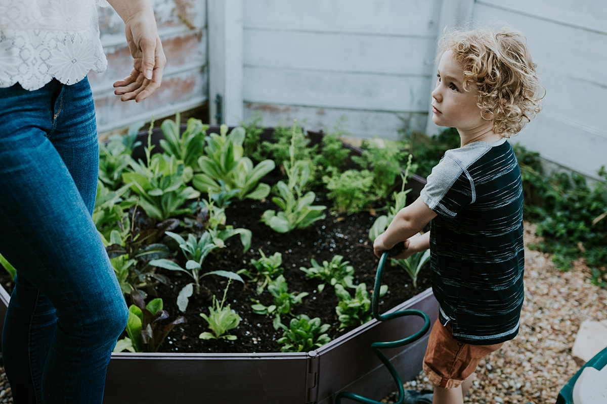Orange County family photographer. Photo of young boy playing in front of his garden