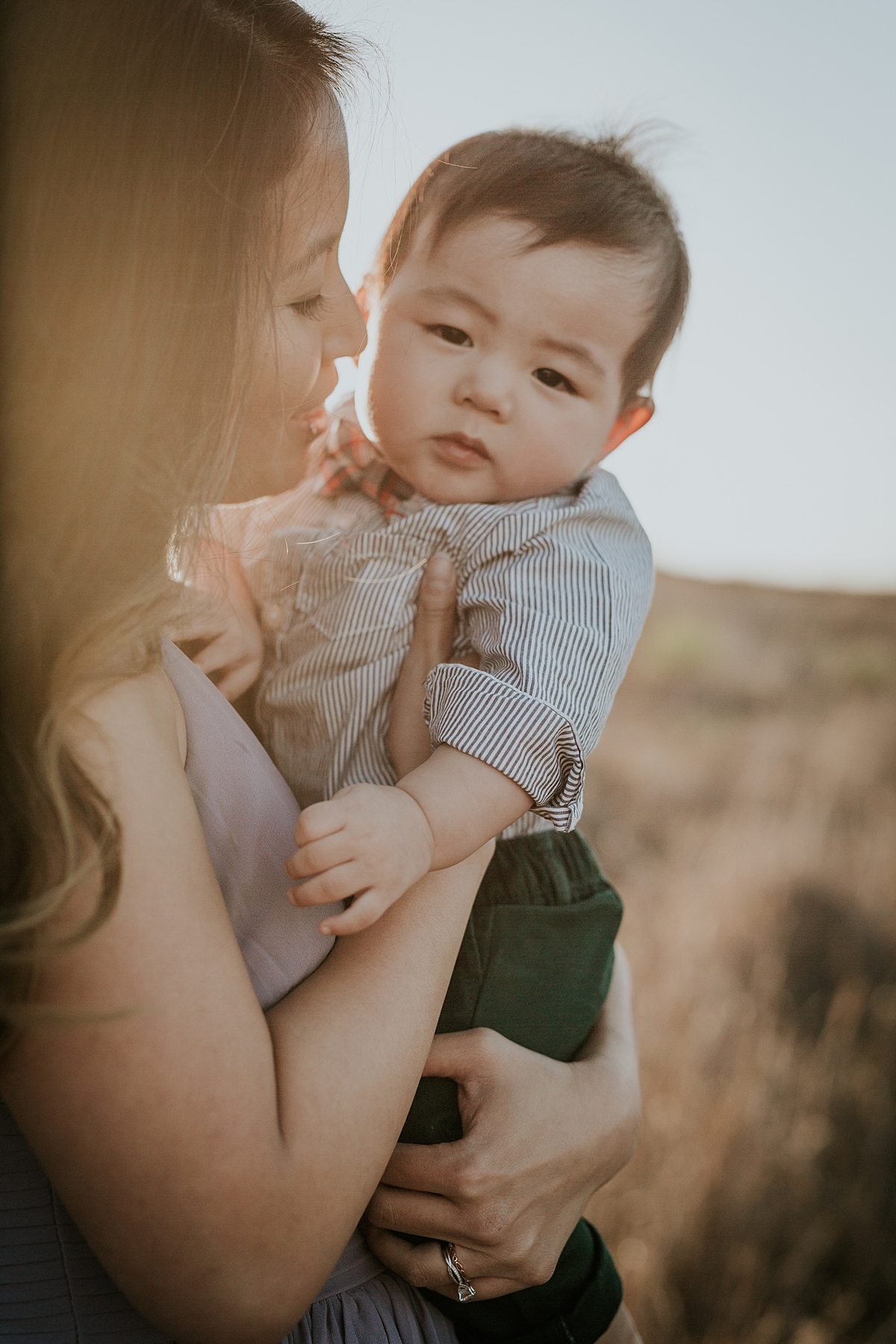Orange County family photographer. Photo of mom in pretty purple dress holding her 8 month old son in blue striped shirt during lifestyle family photo shoot at Quail Hill Trailhead in California