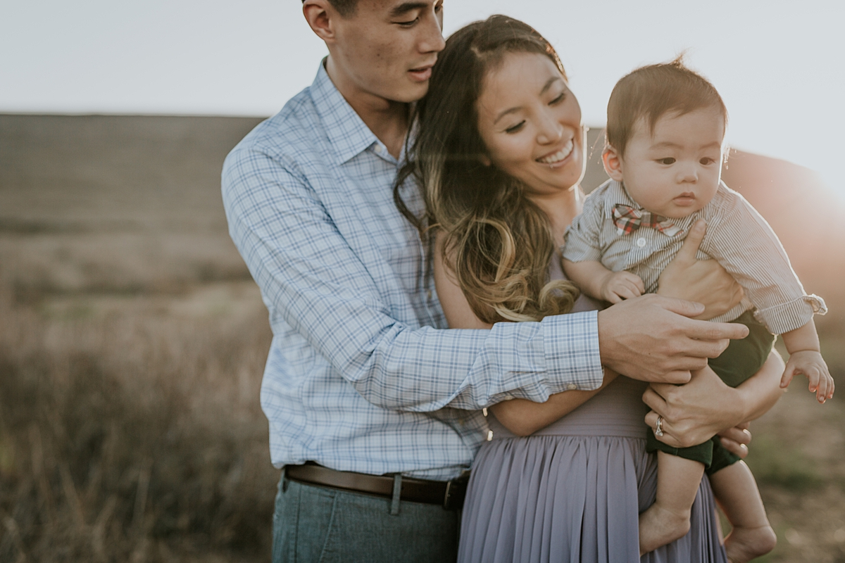 Orange County family photographer. Backlit photo of mom and dad holding their baby boy in a field of yellow grass during lifestyle family photo shoot at Quail Hill Trailhead in California