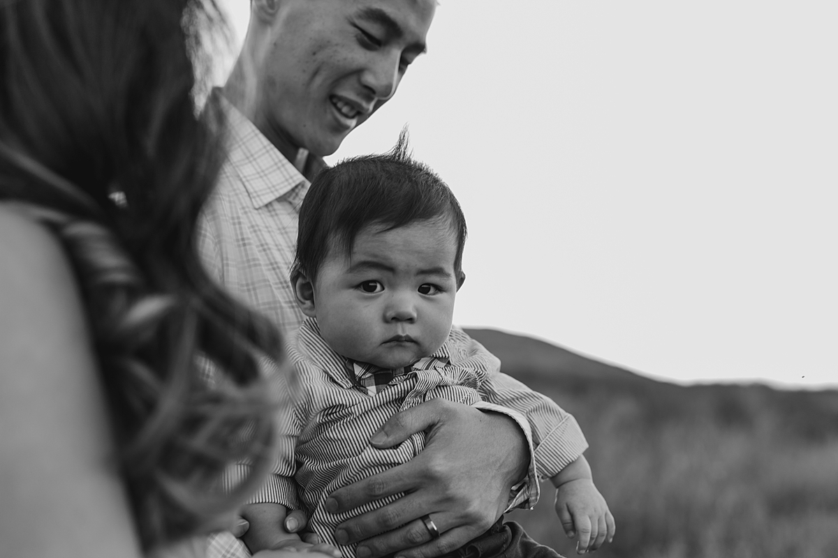 Orange County family photographer. candid black and white photo of dad holding his son in the fields at Quail Hill Trailhead in California