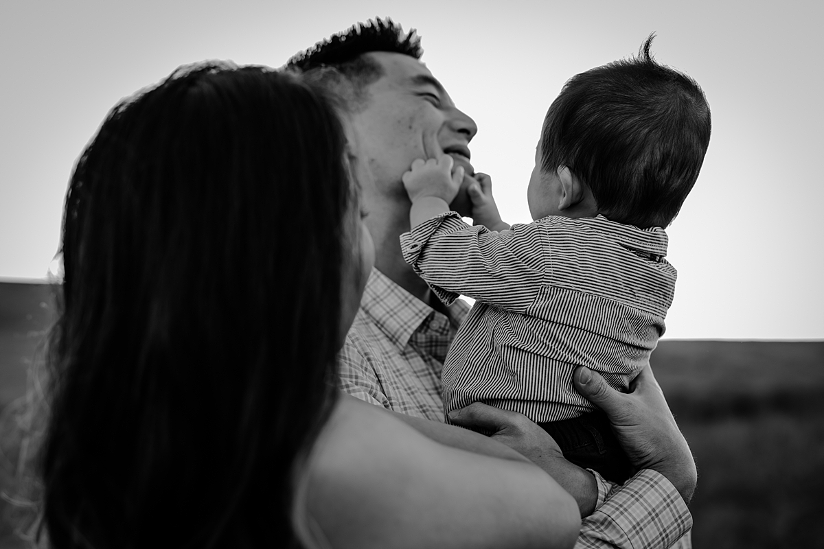 Orange County family photographer. Candid black and white photo of baby boy grabbing onto dad's face during family photo shoot at Quail Hill Trailhead in California