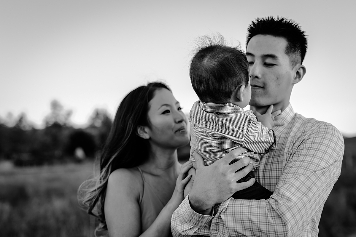 Orange County family photographer. black and white photo of mom and dad holding their baby son as he looks into dad's eyes during family photo shoot at Quail Hill Trailhead in California