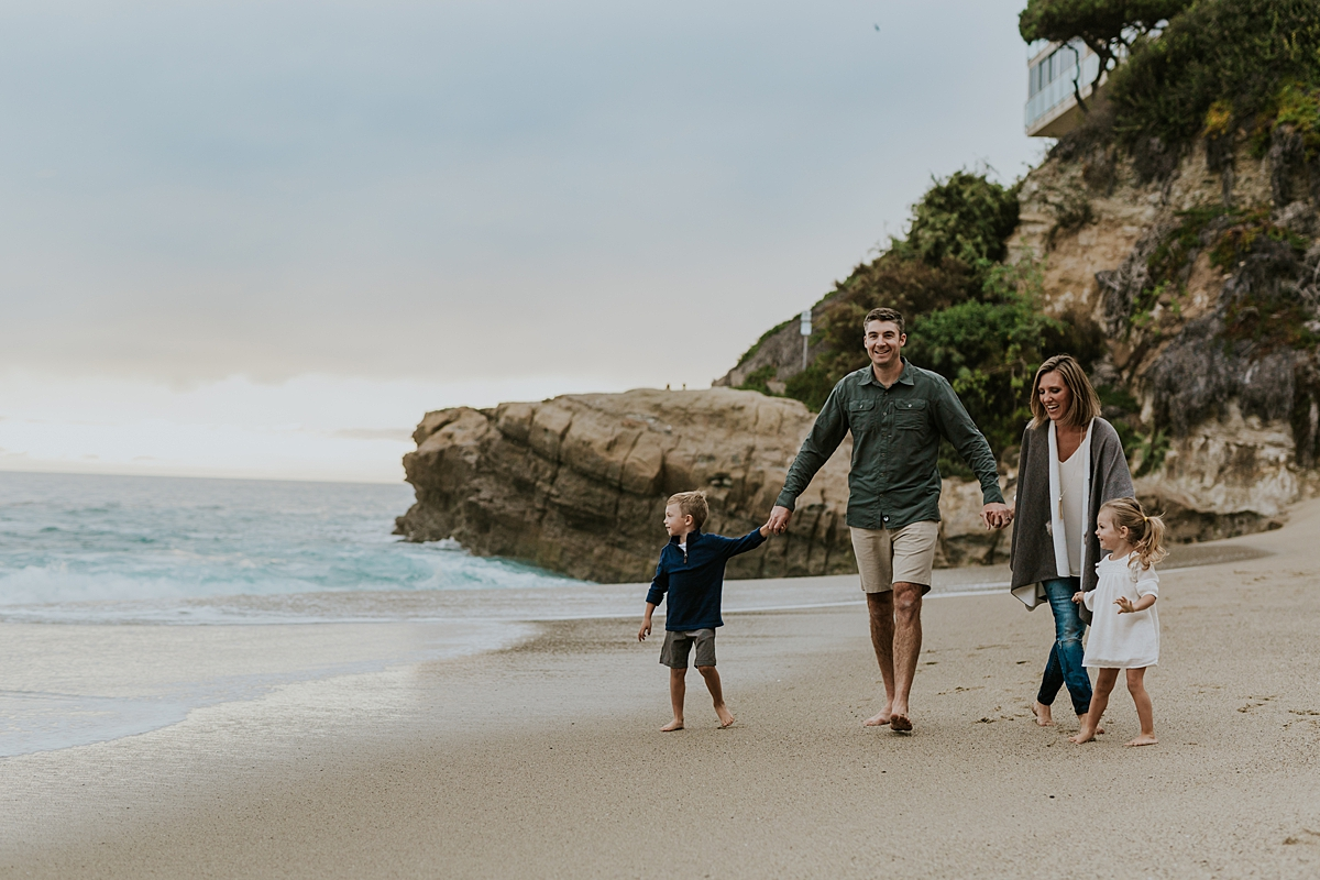 Orange County family photographer. Family of four walk along the sand in front of rock cliffs and ocean at Table Rock Beach, Laguna Beach during family photo session with Krystil McDowall Photography