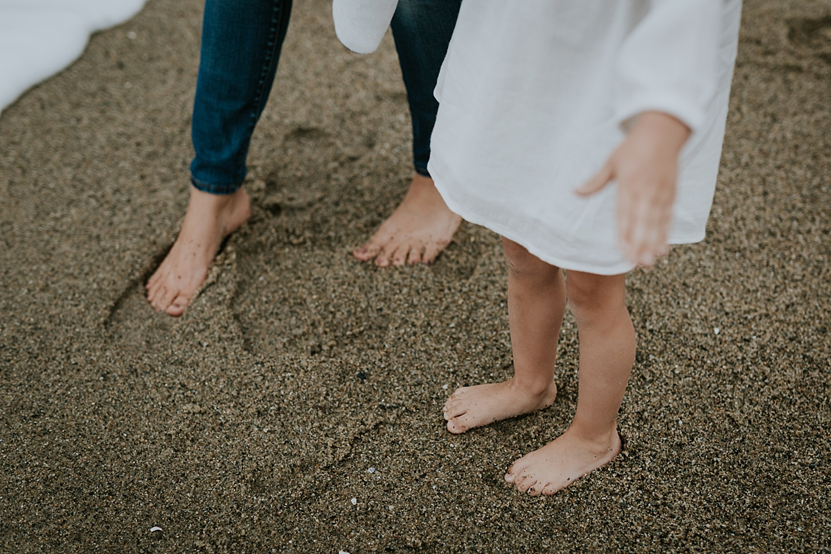 Orange County family photographer. Mom and daughter rub their bare feet in the sand at Table Rock Beach, Laguna Beach during family photo session with Krystil McDowall Photography