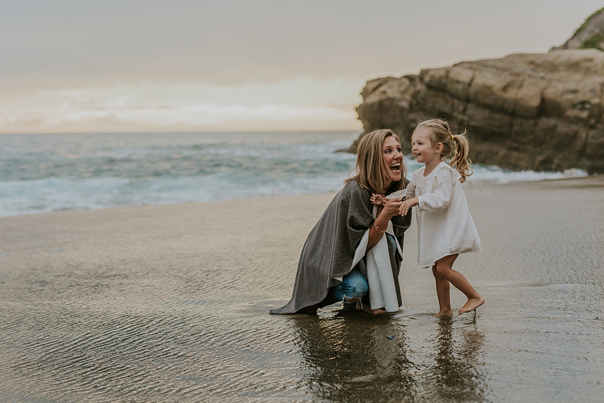 Orange County family photographer. Mom and daughter stand in the sand laughing and smiling and playing witht he ocean waves in the background at Table Rock Beach, Laguna Beach