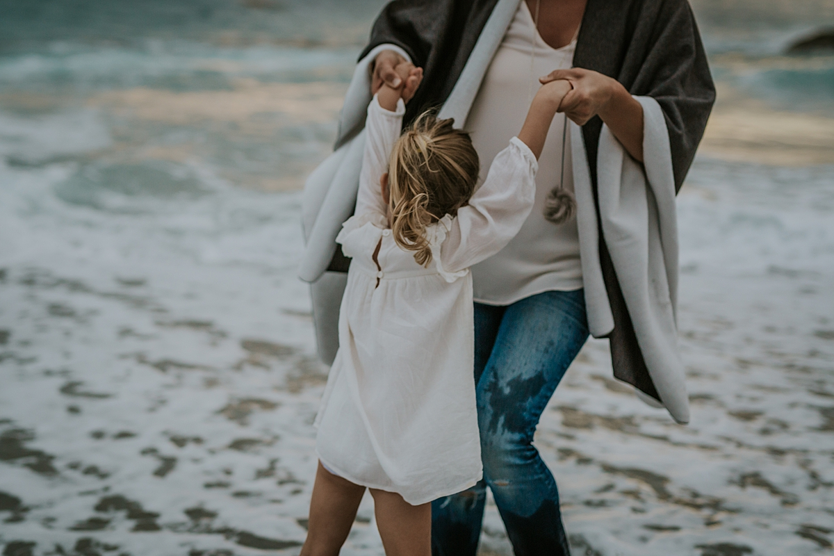 Orange County family photographer. Mom swings daughter around in the ocean waves at Table Rock Beach Laguna Beach during photo session with Krystil McDowall Photography