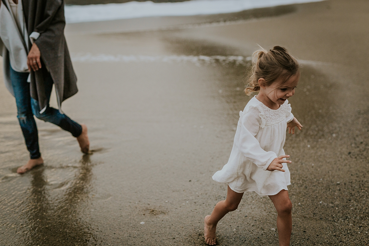 Orange County family photographer. Daughter runs up the beach away from her mama after being swung around during photo session with Krystil McDowall Photography
