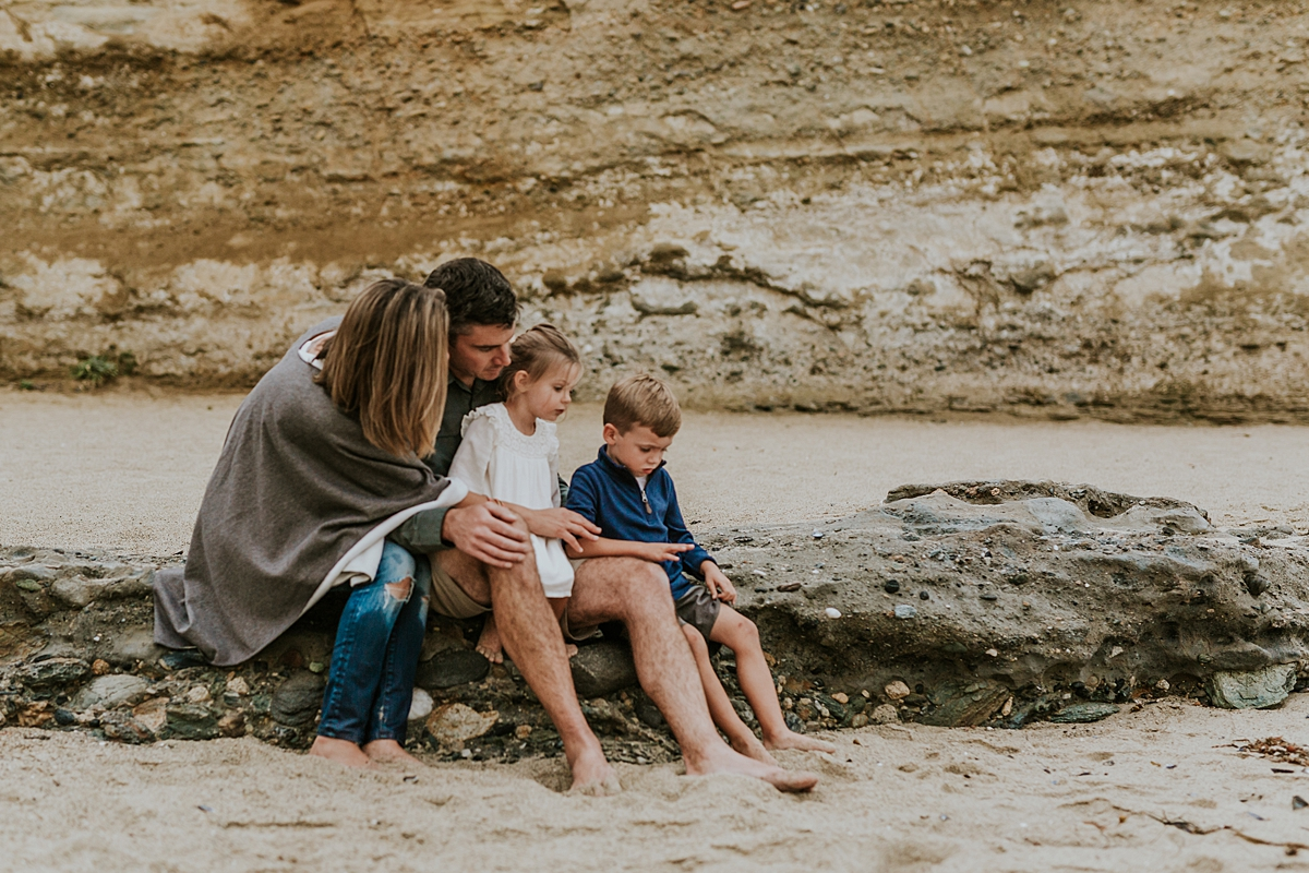 Orange County family photographer. Family of four sit in front of bluffs at Table Rock Beach Laguna Beach during photo session with Krystil McDowall Photography