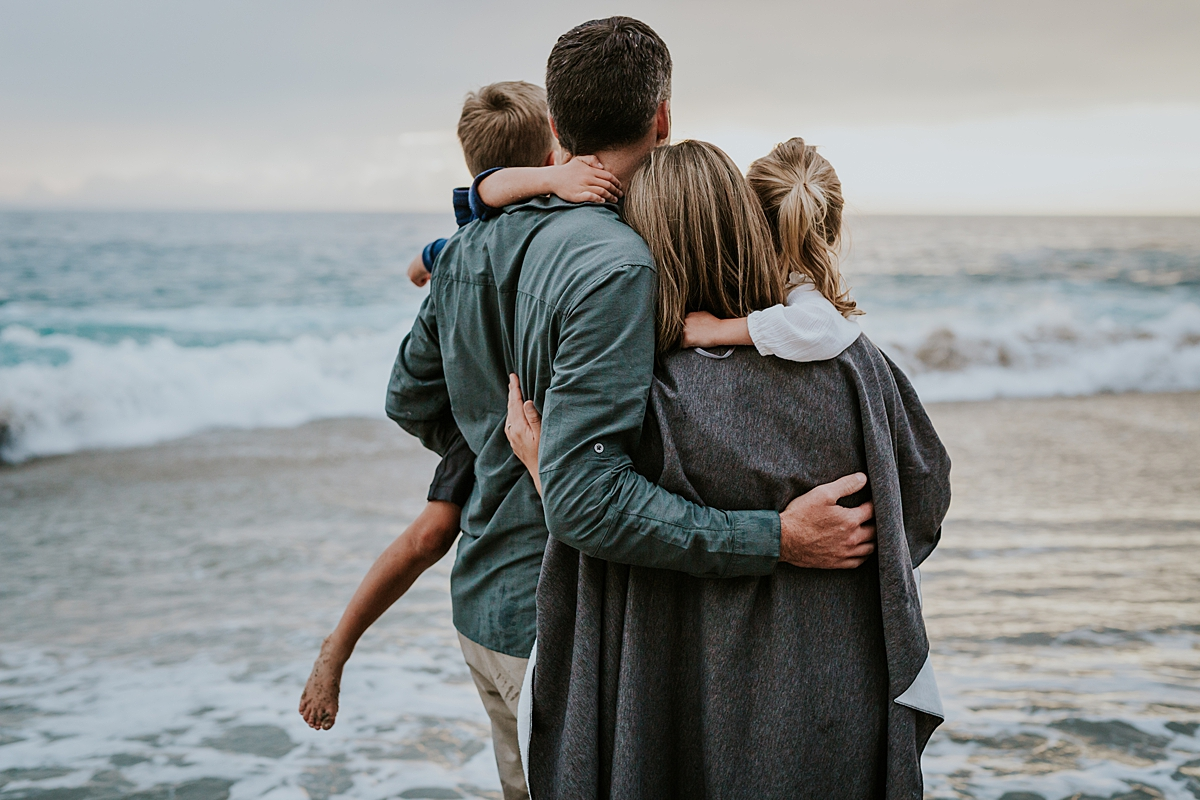 Orange County family photographer. family of four looks out into the sunset at Table Rock Beach Laguna Beach during photo session with Krystil McDowall Photography