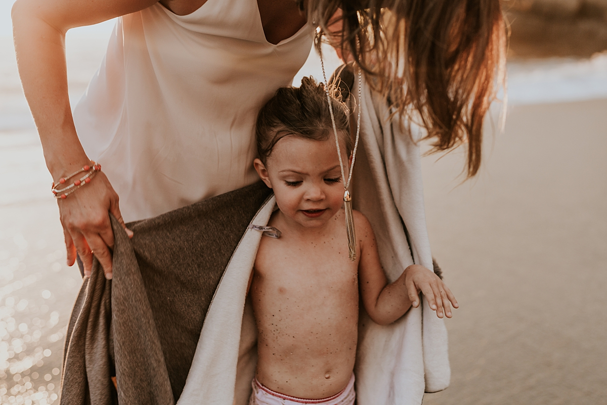 Orange County family photographer. Mom dries off her sweet two year old after she takes a tumble in the waves at Table Rock Beach Laguna Beach during photo session with Krystil McDowall Photography