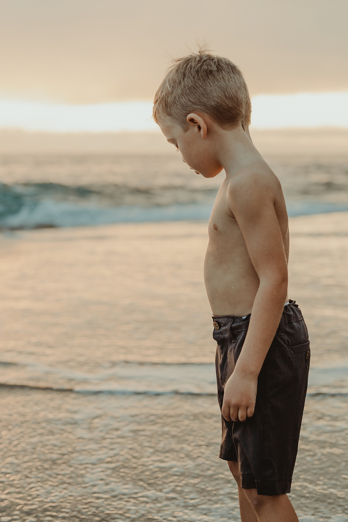 Orange County family photographer. Portrait of shirtless boy looking pensively at the waves at sunset at Table Rock Beach Laguna Beach during photo session with Krystil McDowall Photography