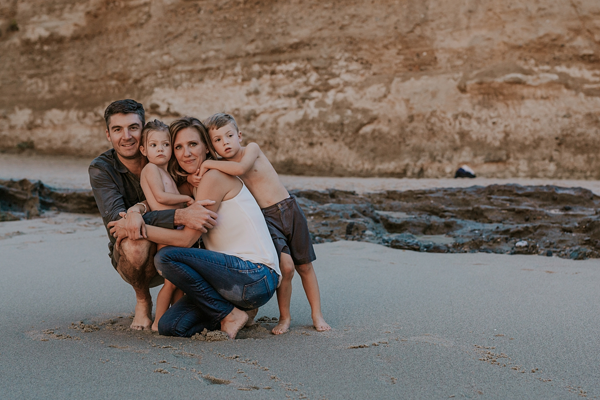 Orange County family photographer. Family photo of mom, dad, son and daughter squatting in front of the bluffs at Table Rock Beach Laguna Beach during photo session with Krystil McDowall Photography