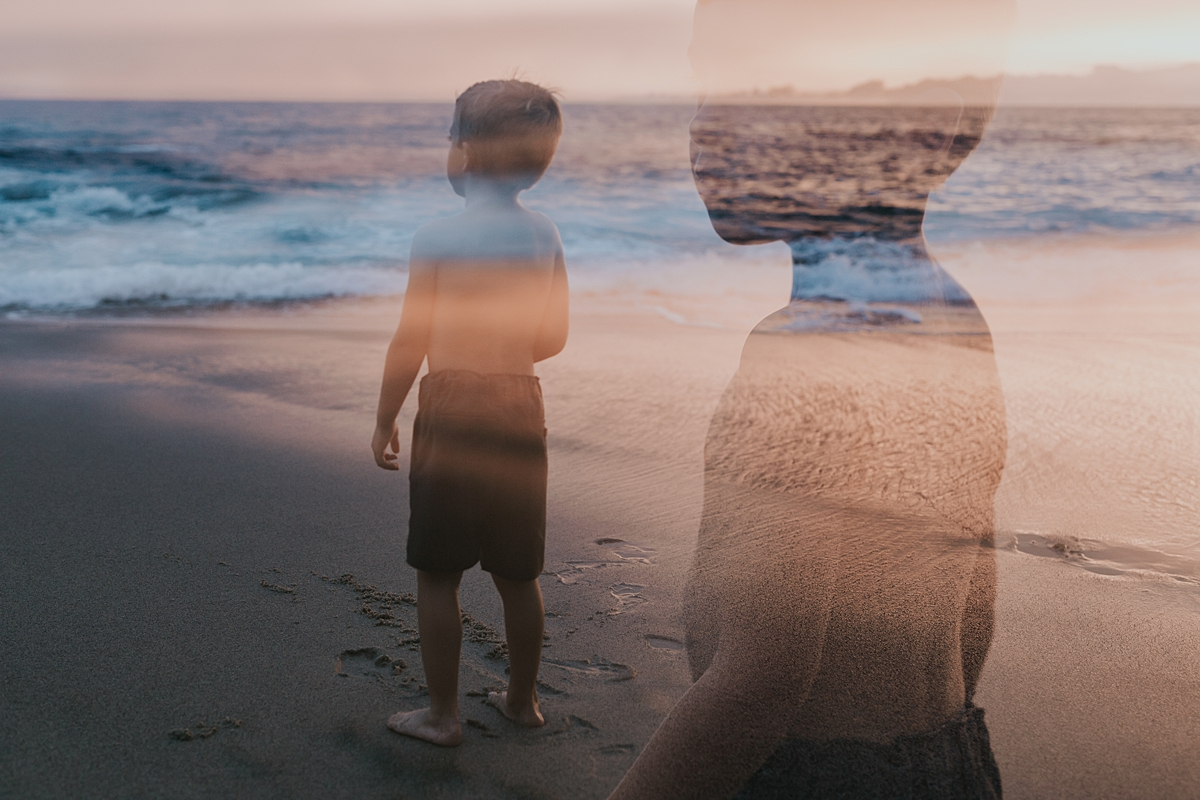Orange County family photographer. Double exposure photo of young boy standing in the shallow waves at Table Rock Beach Laguna Beach during photo session with Krystil McDowall Photography