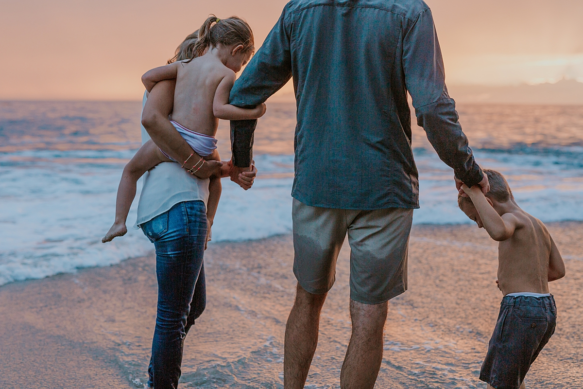Orange County family photographer. Photo of family playing together in shallow ocean waves at sunset at Table Rock Beach Laguna Beach during photo session with Krystil McDowall Photography