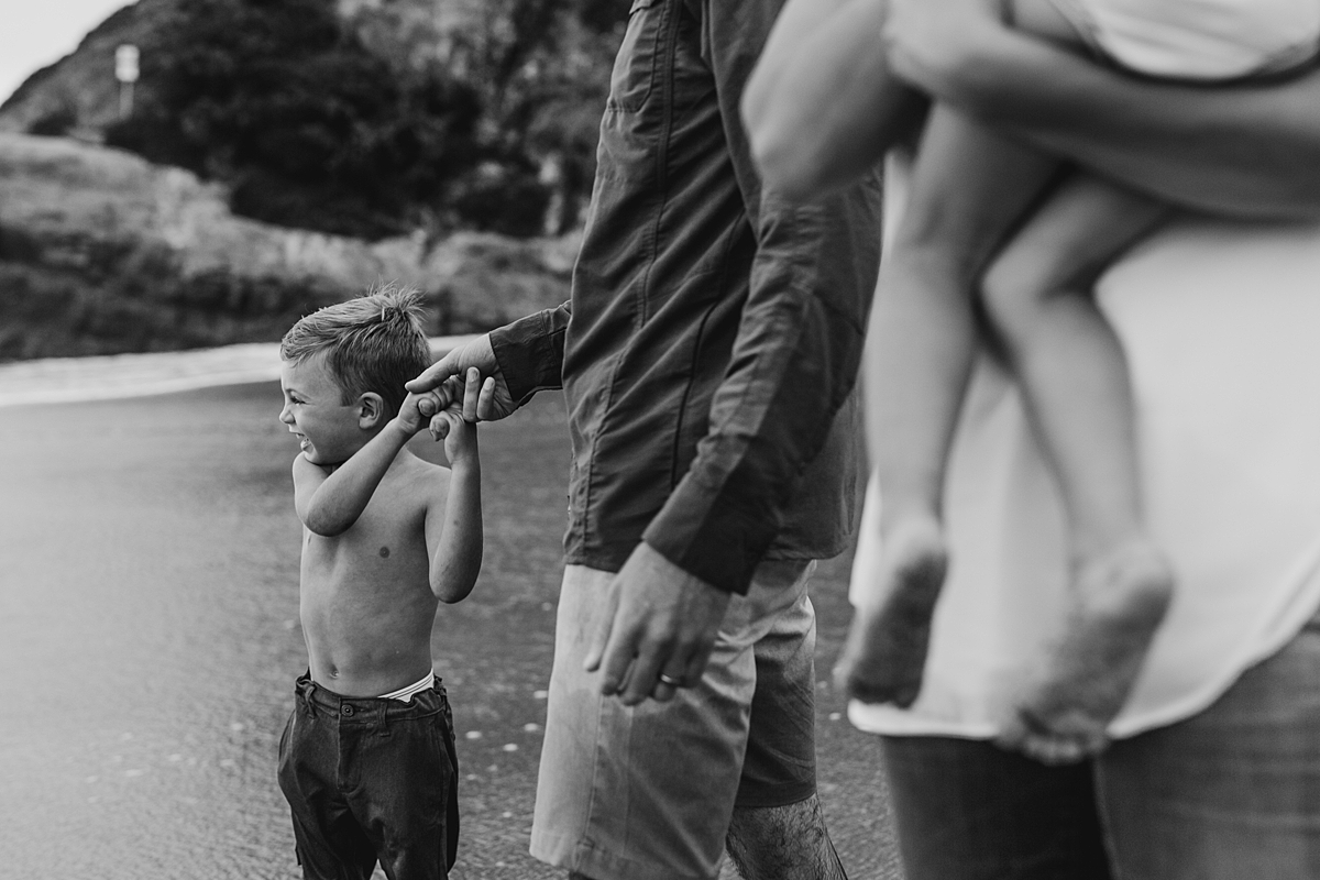 Orange County family photographer. Black and white photo of young boy holding dad's hand as they look out at the ocean