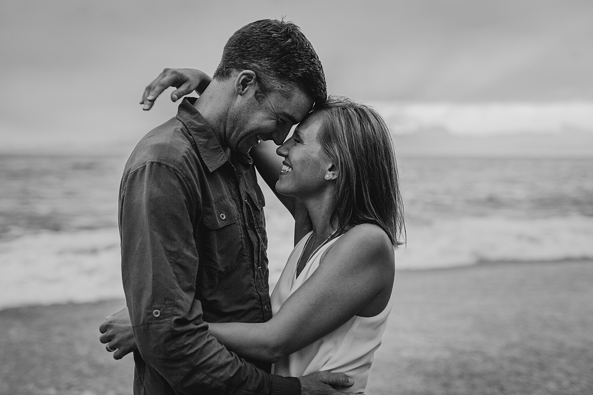Orange County family photographer. Photo of mom and dad embracing on the beach as the sunsets at Table Rock Beach Laguna Beach during photo session with Krystil McDowall Photography