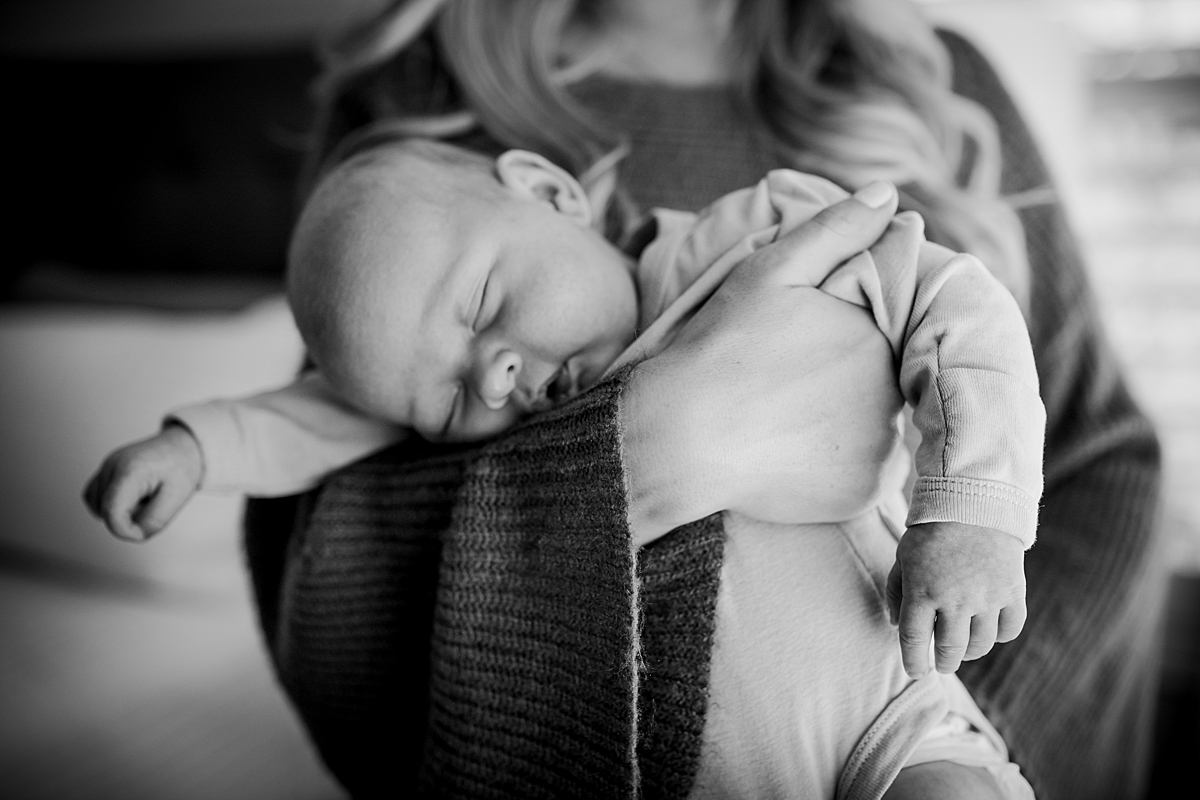 Orange County family photographer. Mom holds sleeping newborn son in her arms during in-home newborn session with Krystil McDowall Photography