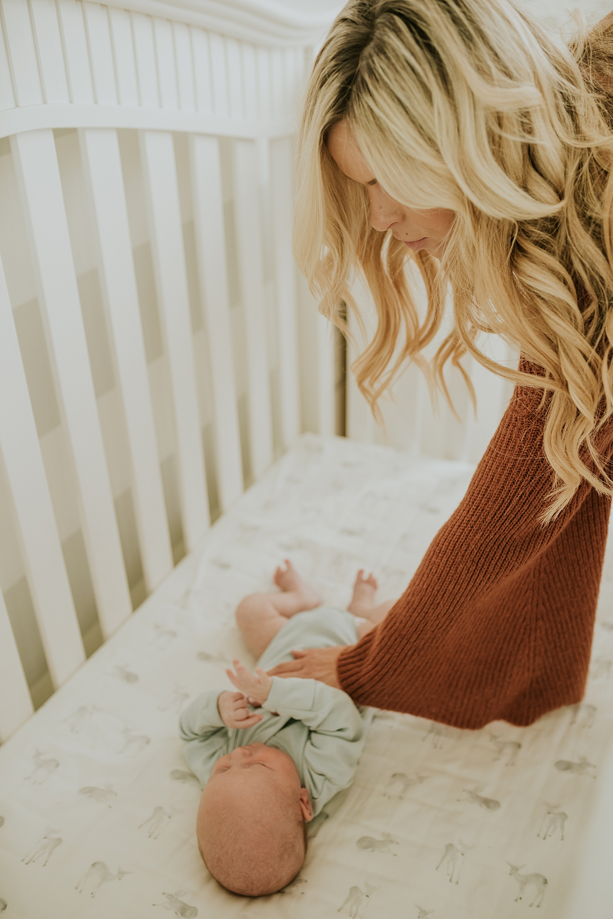 Orange County family photographer. Newborn boy lays in his bed while mom reaches over the crib to caress him during in-home newborn session with Krystil McDowall Photography