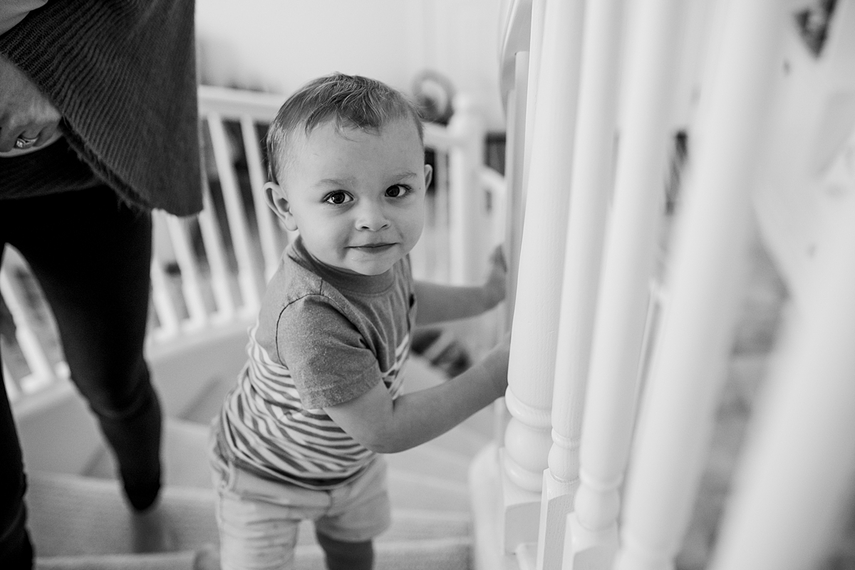 Orange County family photographer. photo of older brother coming up the stairs during in-home newborn session with Krystil McDowall Photography