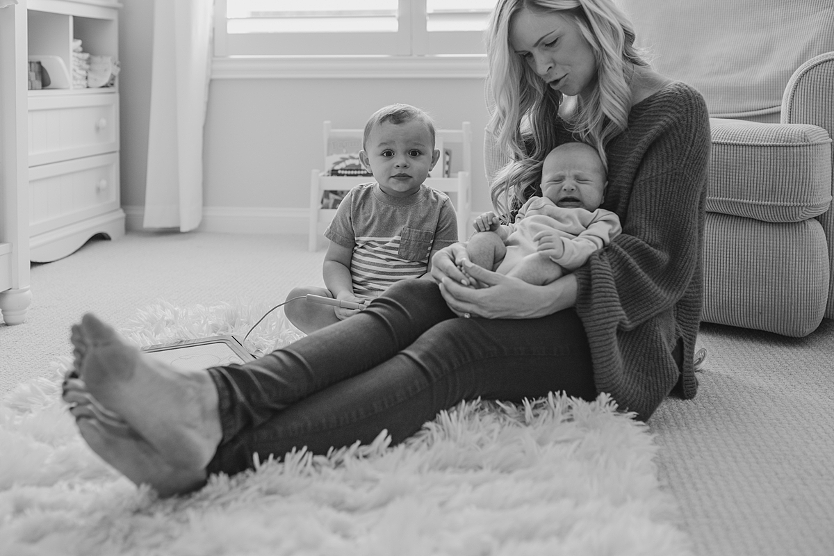 Orange County family photographer. Mom, older son and newborn boy sit together to read a story during in-home newborn session with Krystil McDowall Photography