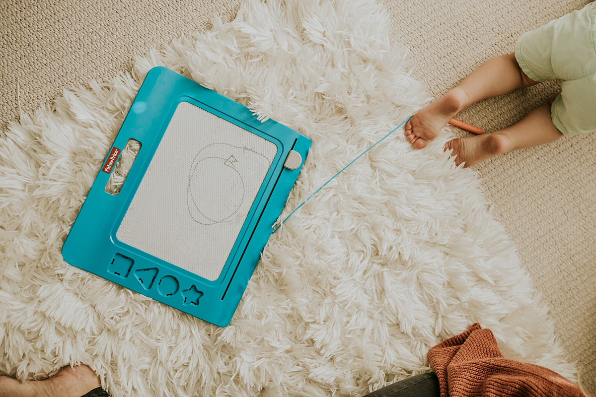 Orange County family photographer. Photo of toddler feet walking away from doodle pro toy