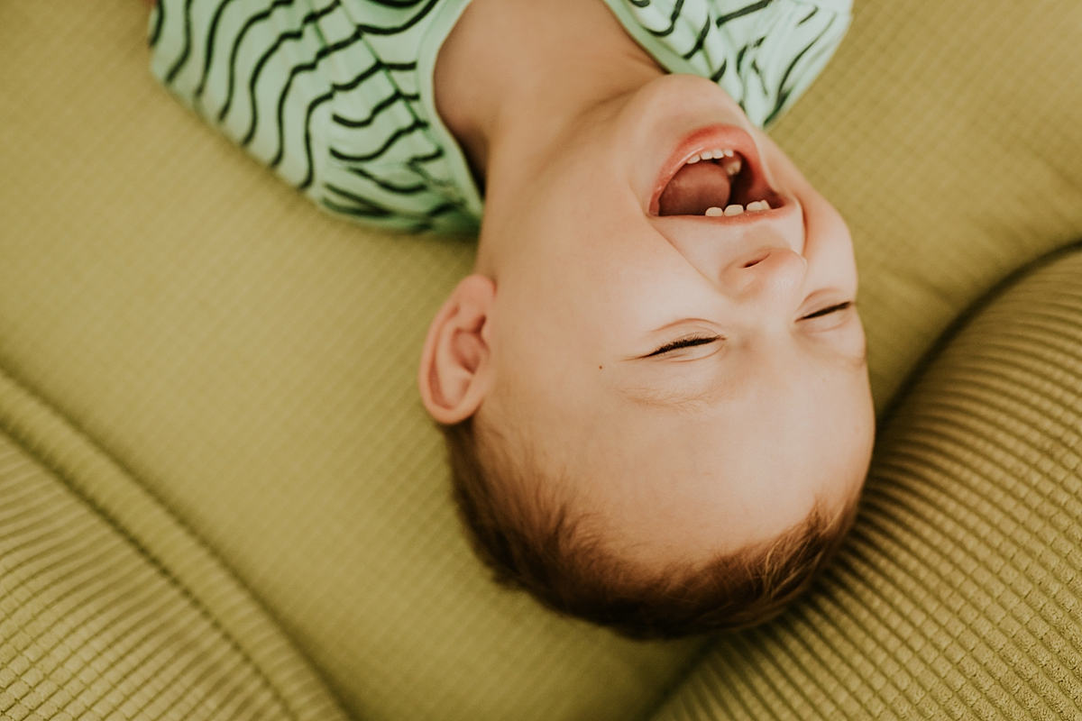 Orange County family photographer. photo of toddler laughing his sweet little head off during in-home newborn session with Krystil McDowall Photography