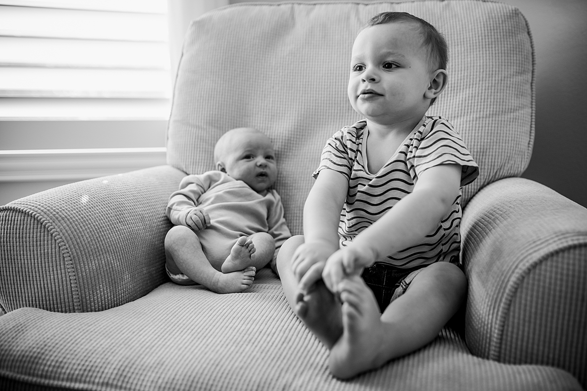 Orange County family photographer. Candid portrait of toddler and his newborn brother sitting in a chair in the baby room during in-home newborn session with Krystil McDowall Photography