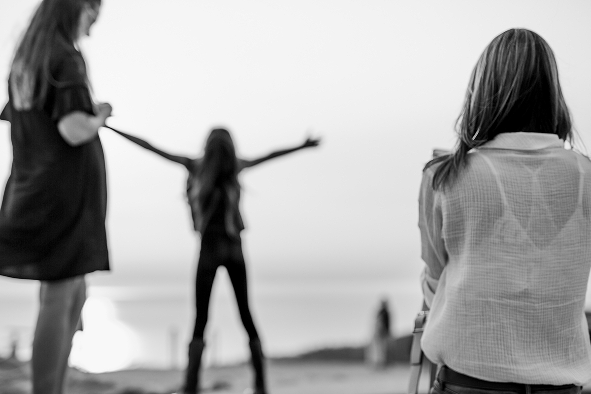 Orange County family photographer. Candid image of daughter doing queen of the world pose at Top of the World Laguna Beach