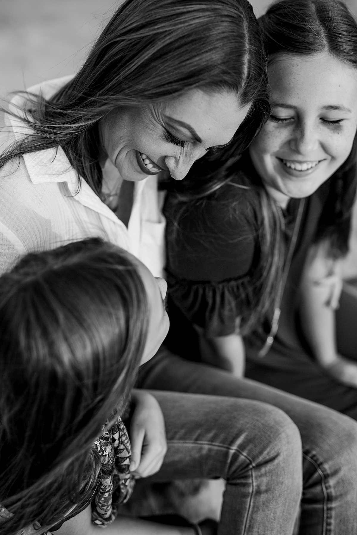 Orange County family photographer. Black and white image of mom chatting with her daughters during candid family photo session at Top of the World Laguna Beach