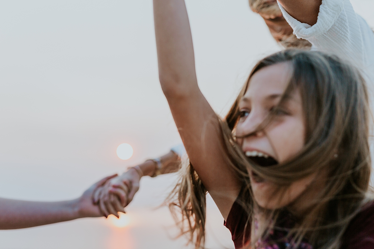 Orange County family photographer. Photo of mom and her daughters holding hands and skipping around laughing during candid family photo session at Top of the World Laguna Beach
