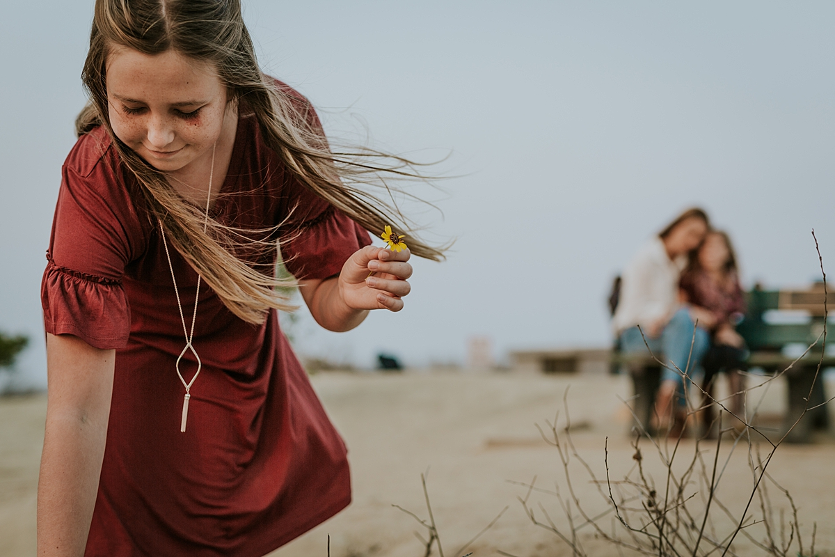 Orange County family photographer. Photo of girl picking flowers while her mom and younger sister sit behind on bench during candid family photo session at Top of the World Laguna Beach