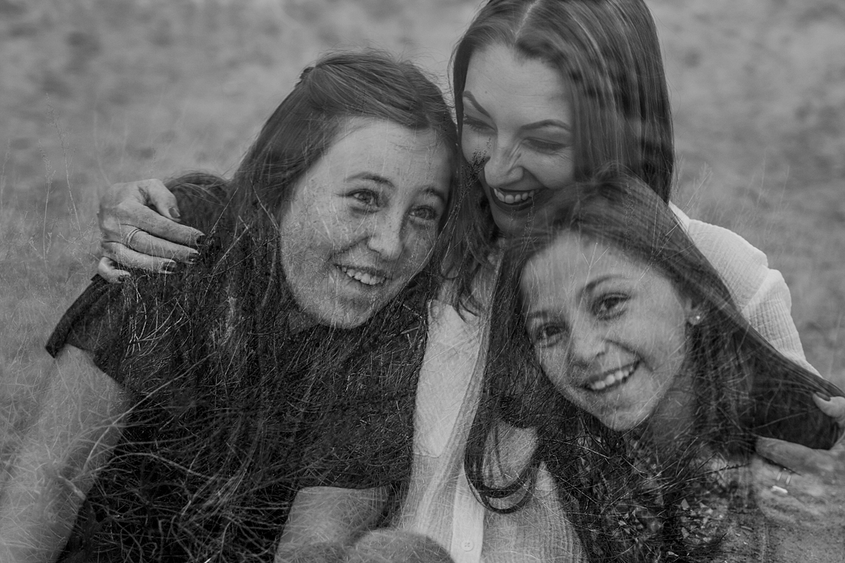 Orange County family photographer. Double exposure photo of mom and her daughters laughing during candid family photo shoot at Top of the World Laguna Beach by Krystil McDowall Photography