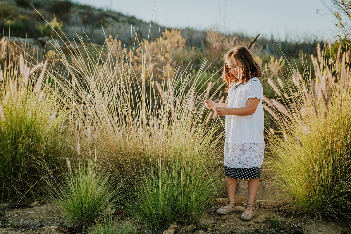 Orange County family photographer. Photo of beautiful 5 year old girl in white dress picking the dandelions at sunset at family photo shoot at Quail Hill