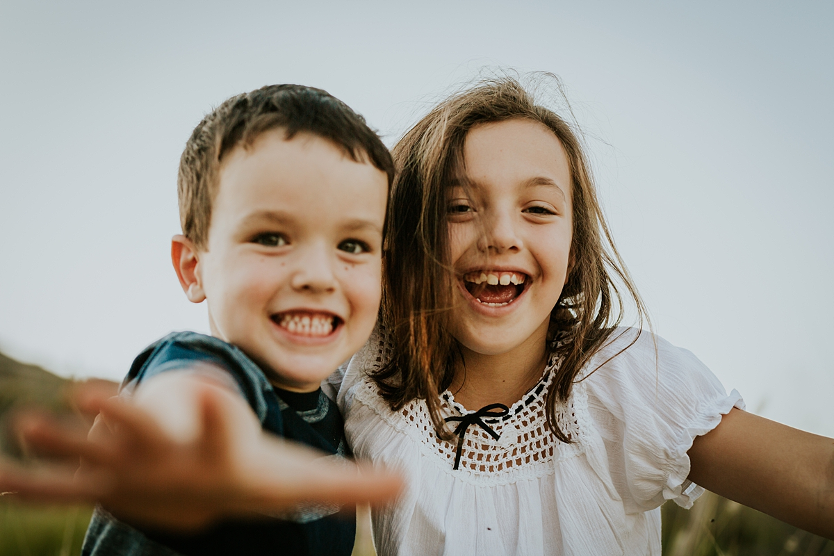 Orange County family photographer. Candid photo of brother and sister laughing and reaching for the camera at family photo shoot at Quail Hill