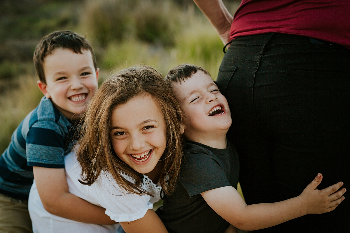 Orange County family photographer. Candid photo of brothers and sister laughing and mucking around at family photo shoot at Quail Hill
