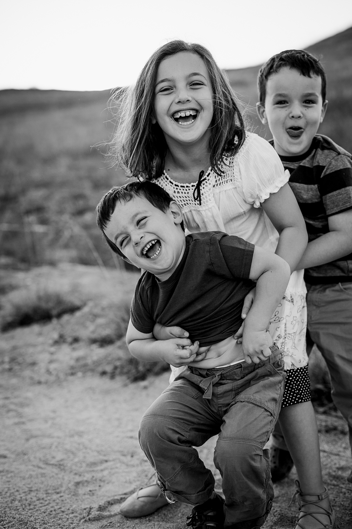Orange County family photographer. Black and white portrait of brothers and sister laughing and mucking around at family photo shoot at Quail Hill