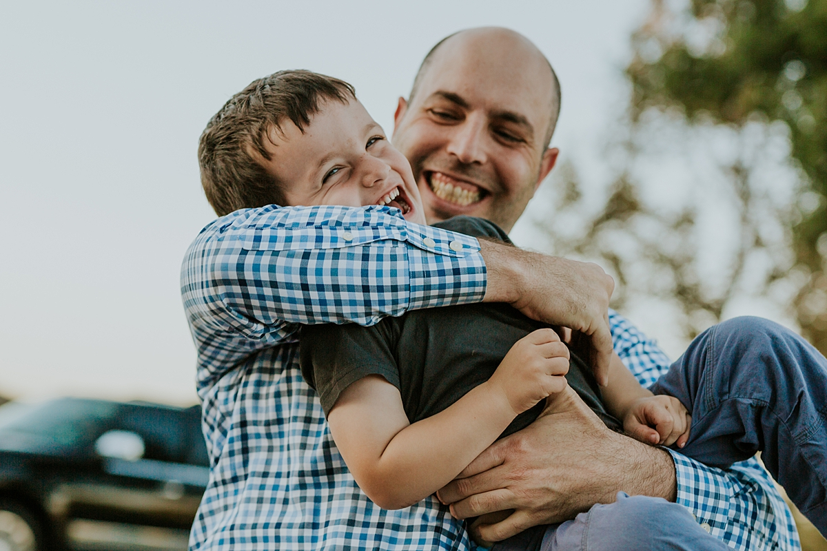 Orange County family photographer. Candid photo of dad tickling his youngest son during family photo shoot at Quail Hill with Krystil McDowall Photography