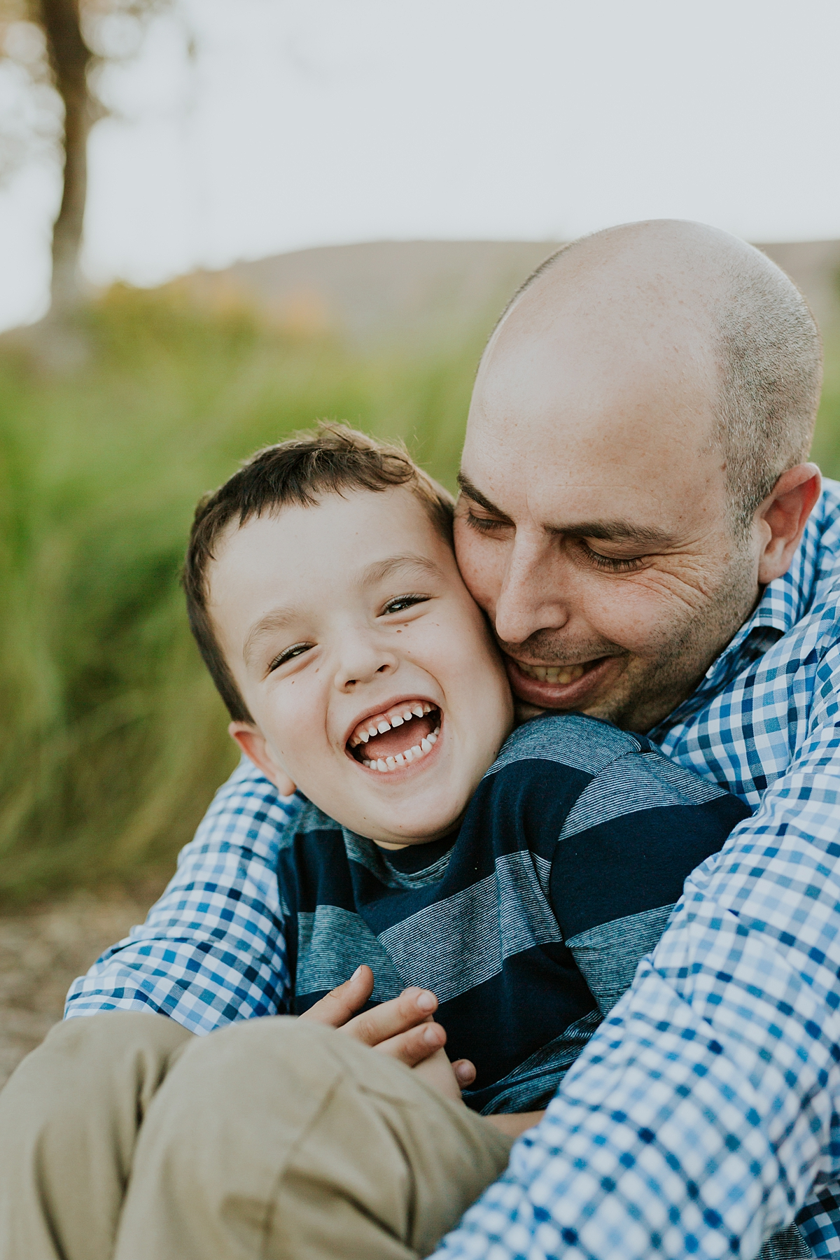 Orange County family photographer. Candid photo of dad and oldest son laughing during family photo shoot at Quail Hill by Krystil McDowall Photography