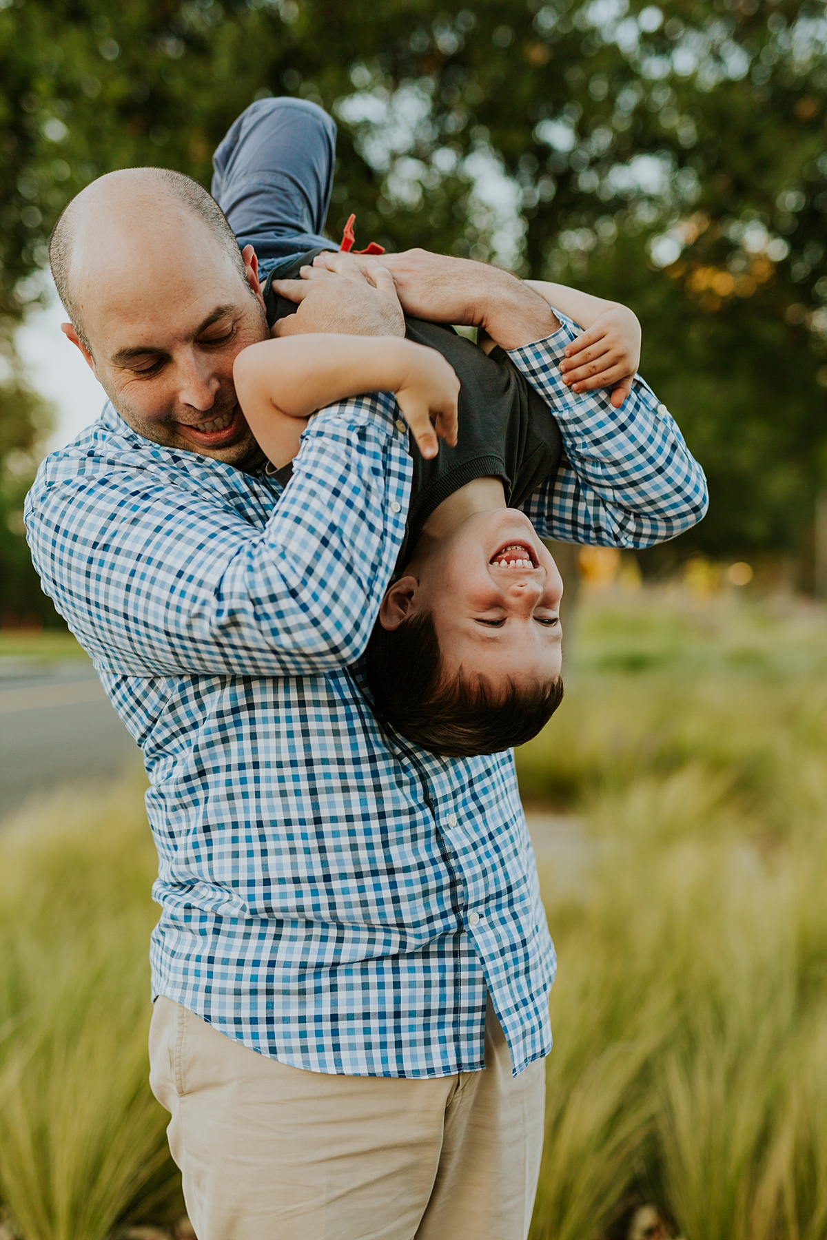 Orange County family photographer. Photo of dad playing with his son by tipping him upside down during family photo shoot at Quail Hill