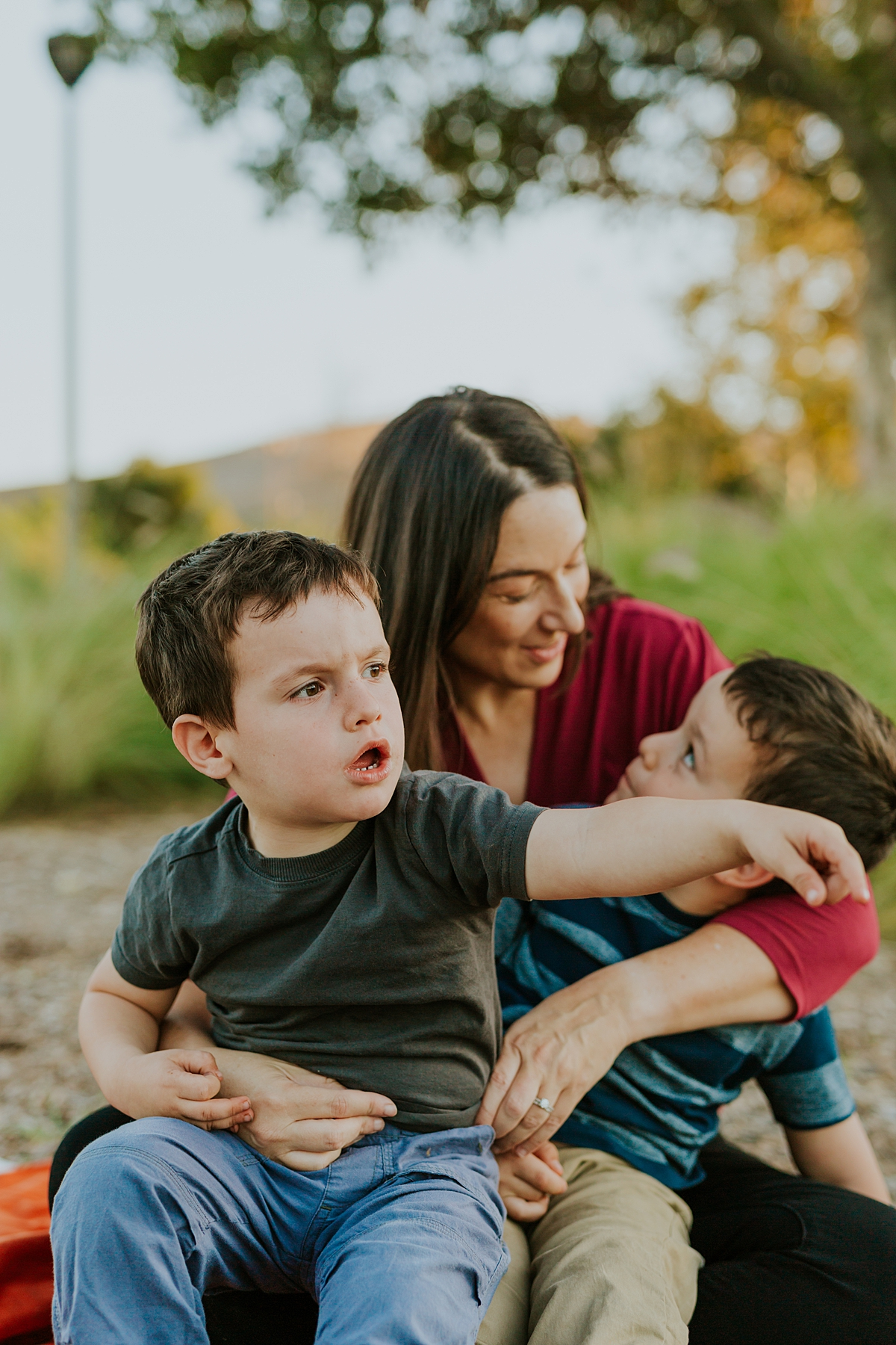 Orange County family photographer. Candid photo of mom and her two boys sitting on her lap during family photo shoot at Quail Hill with Krystil McDowall