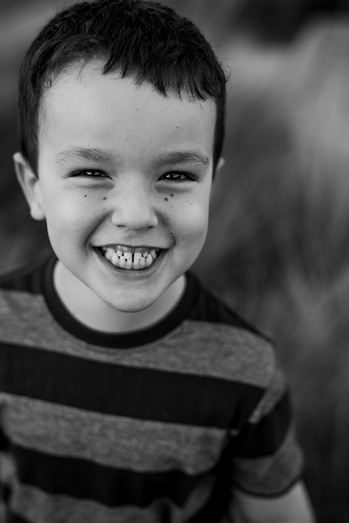 Orange County family photographer. Black and white portrait of young boy standing in tall green grass during family photo shoot at Quail Hill with Krystil McDowall Photography