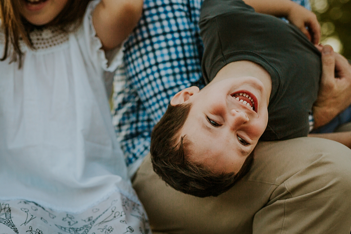 Orange County family photographer. Candid photo young boy strewn across his dad's lap laughing during family photo shoot at Quail Hill with Krystil McDowall Photography