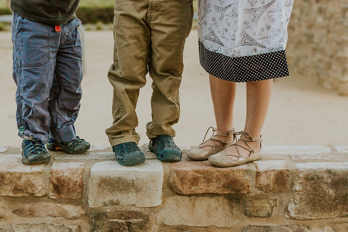 Orange County family photographer. Photo of sibling feet as they stand on a stone wall during family photo shoot at Quail Hill with Krystil McDowall