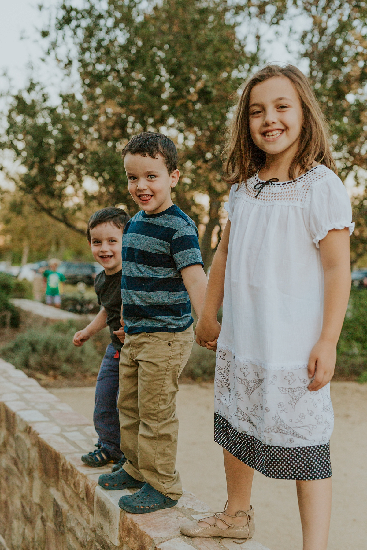 Orange County family photographer. photo of siblings hand-in-hand standing on stone a wall during family photo shoot at Quail Hill with Krystil McDowall Photography
